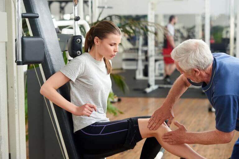 ung kvinde der får undrsøgt knæ i fitnesscenter