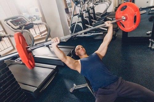 Mand laver bænkpres i fitnesscenteret