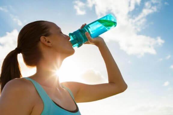 kvinde der drikker af vandflaske