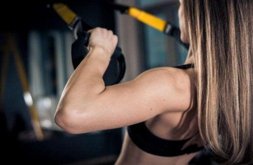 kvinde der træner med TRX