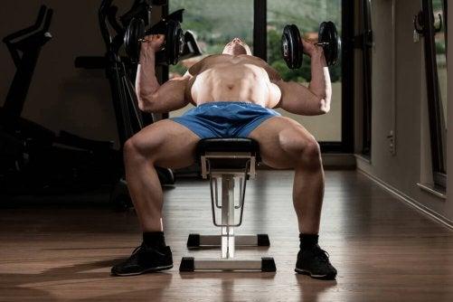 mand der laver brystpres med håndvægte