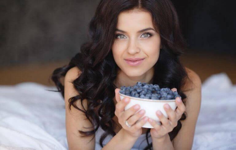 kvinde der holder en skål med blåbær