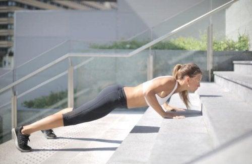 kvinde der laver push-ups på trappe