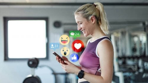 kvinde der bruger sin mobil i fitness