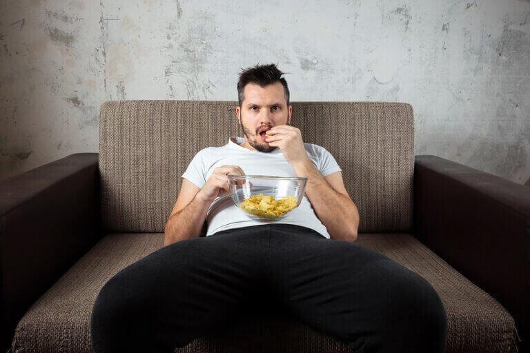 mand der spiser chips i sofa
