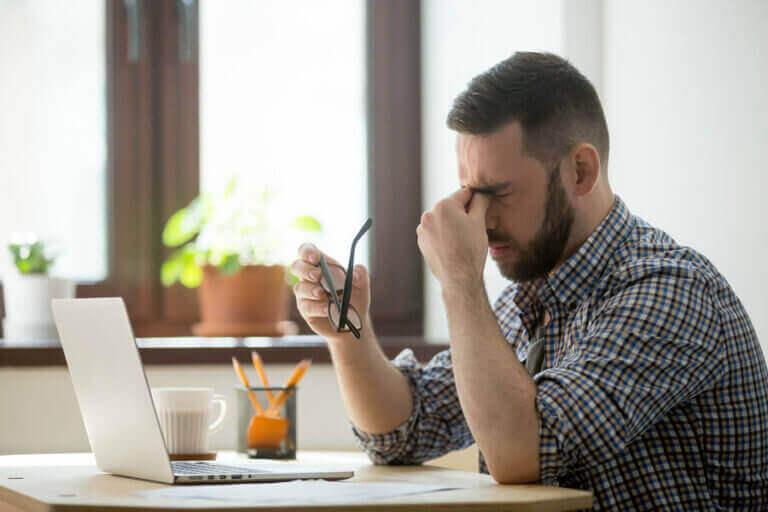 mand med hovedpine foran computer
