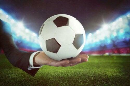 mand med en fodbold på håndfladen