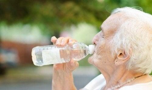 Ældre kvinde drikker en flaske vand