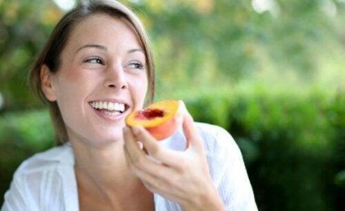 kvinde der spiser en fersken