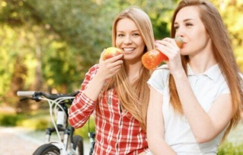 kvinder der spiser frugt og drikker juice