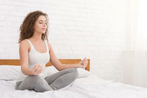 kvinde der mediterer i seng
