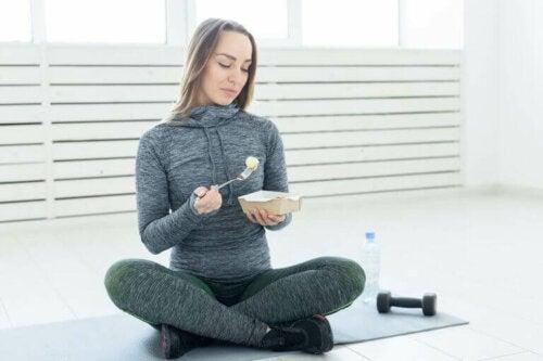 kvinde der spiser i fitnesstøj
