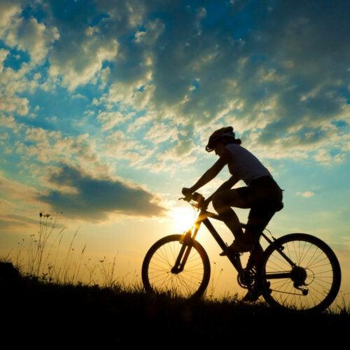 kvinde der cykler i naturen