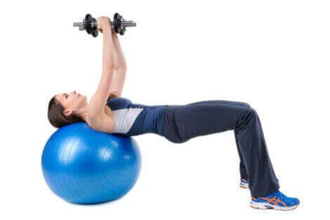 kvinde der træner med håndvægte på bold