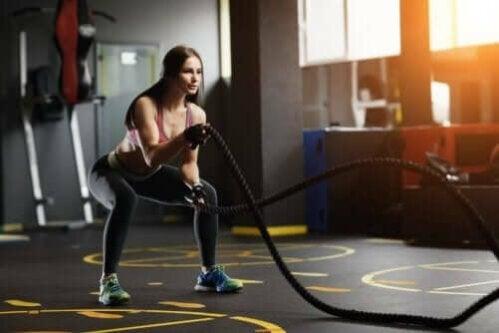 kvinde der træner med et battle rope