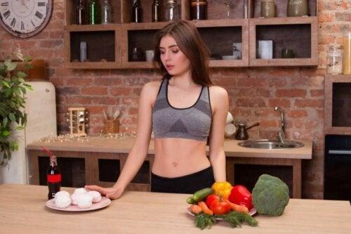 kvinde der står ved sund og usund tallerken