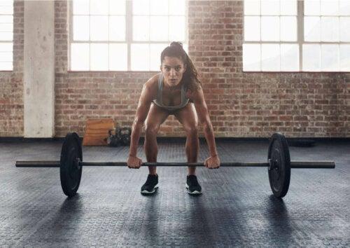 kvinde der træner med en vægtstang