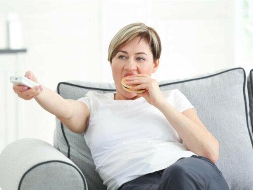 kvinde der spiser bruger og ser fjernsyn