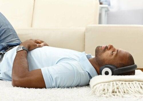 mand der ligger og hører musik