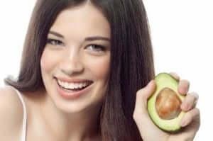 kvinde der holder en halv avocado