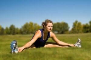 kvinde der laver udstræk for at forbedre sine lårs fleksibilitet