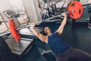 mand der udfører brystpres med en vægtstang
