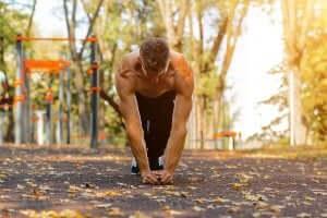 mand der udfører push-ups med smalt greb udenfor
