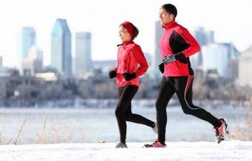 Mand og kvinde løber i vintervejret