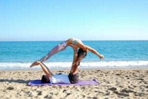 mand og kvinde dyrker en akroyogastilling til begyndere på stranden