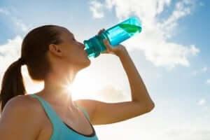 kvinde drikker vand fra dunk