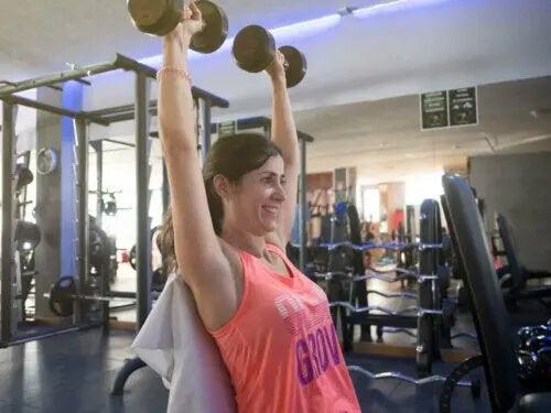 Kvinde, der træner skuldrene med håndvægte