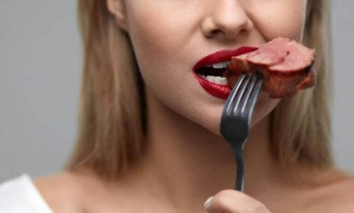 Frau isst Fleisch