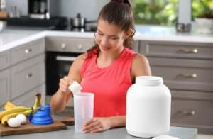 Nahrungsergänzungsmittel - Frau bei der Zubereitung in der Küche