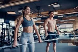 Schulterheben - Frau und Mann mit Hantelstange