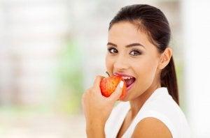 Une femme croque dans une pomme