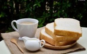 Tasse de café avec du lait et des tartines de pain