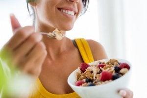 Femme qui mange un bol de céréales complètes avec des fruits pendant les règles