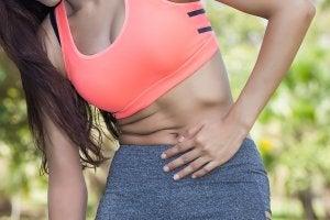 Femme sportive avec des douleurs au ventre.