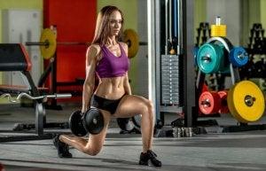 Femme dans une salle de sport, exercice de fente avant avec poids.