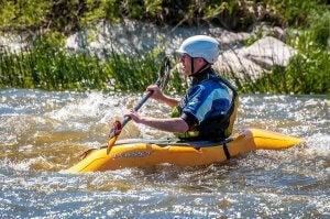 Un homme sur un canoë-kayak qui fait du rafting.