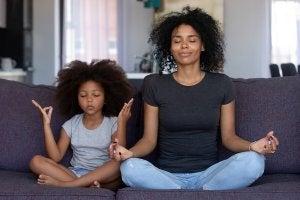 une mère et sa fille en train de méditer