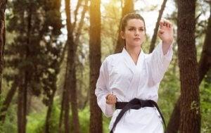 Une femme qui pratique le judo dans la forêt.