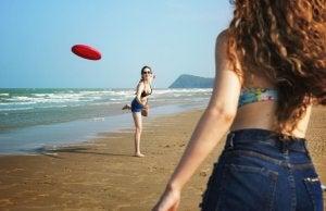 deux femmes qui jouent au frisbee à la plage.