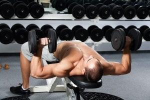 Homme qui se muscle avec des haltères dans une salle de sport.