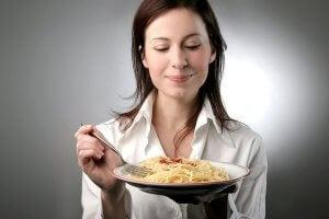 Une femme qui mange des pâtes
