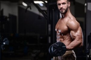 Homme en salle de fitness qui travaille sa force musculaire avec des haltères.