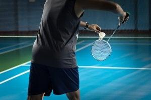 Un homme qui joue au badminton, l'un des sports de raquette les plus connus.