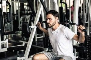 Homme dans une salle de sport qui effectue un tirage poitrine.