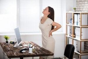 Une femme au travail qui souffre de douleur au dos.