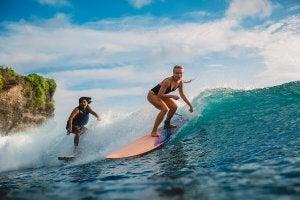 Deux femmes qui font du surf, le premier des sports de glisse.